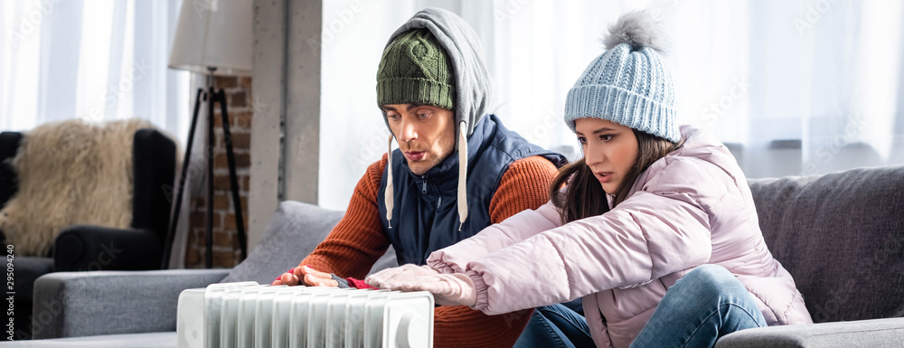 Fototapety, obrazy: panoramic shot of girlfriend and boyfriend in winter outfit warming up near heater