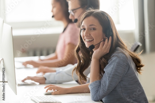 Call center employee female sitting at workplace pose for camera Fototapet
