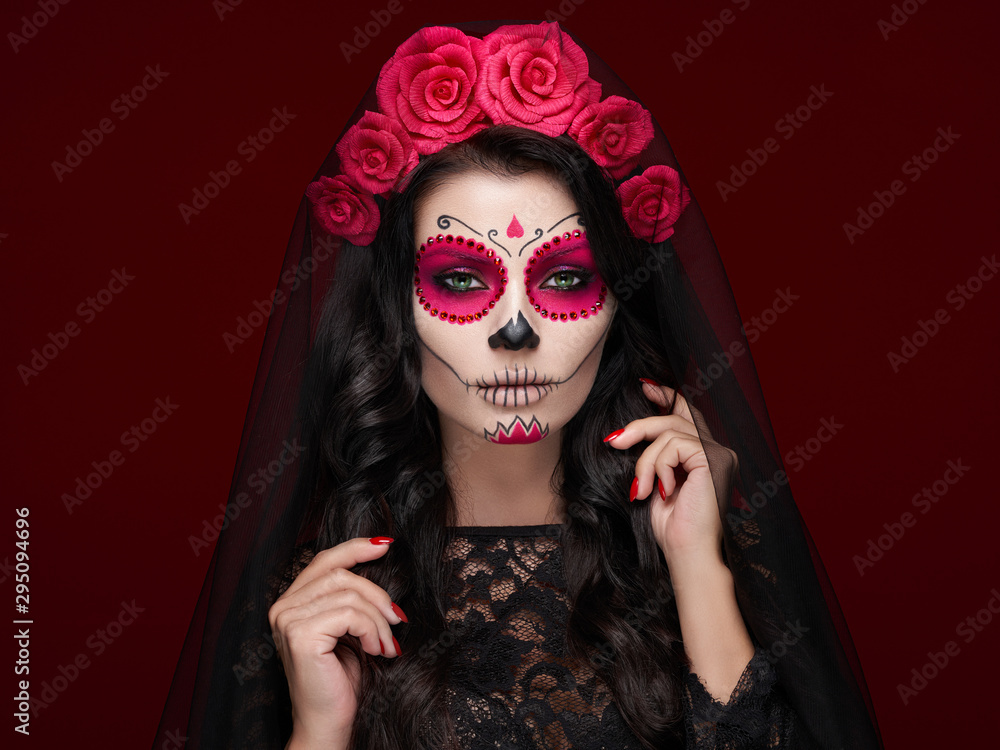 Fototapeta Portrait of a woman with sugar skull makeup over red background. Halloween costume and make-up. Portrait of Calavera Catrina