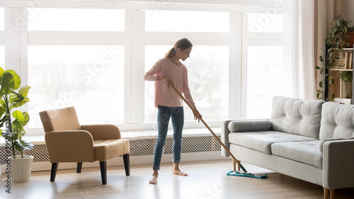 Obraz na plátně Young woman housewife clean floor in modern living room