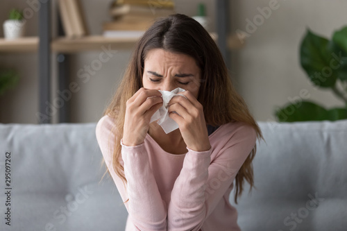 Allergic ill woman holding tissue blowing running nose Canvas Print