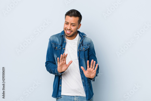 Fotografie, Tablou  Young handsome filipino man rejecting someone showing a gesture of disgust