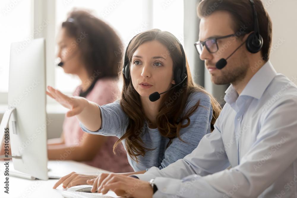Fototapeta Call center female worker helping to man new employee colleague