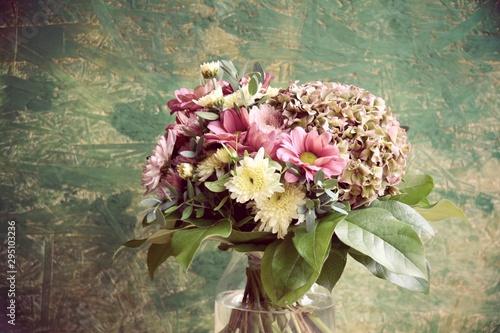 Papiers peints Fleur Schöner Blumenstrauß mit Herbstblumen vor rustikalem grünem Hintergrund