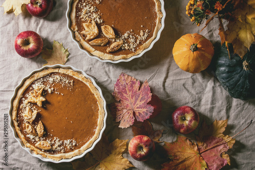 Foto auf Gartenposter Brot Traditional homemade autumn pumpkin pies for Thanksgiving or Halloween dinner served in ceramic dish with yellow autumn leaves, pumpkins and apples on linen table cloth. Dark rustic style. Flat lay