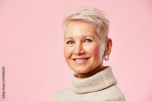 Portrait of mature woman with short blond hair and in beautiful earrings smiling Wallpaper Mural