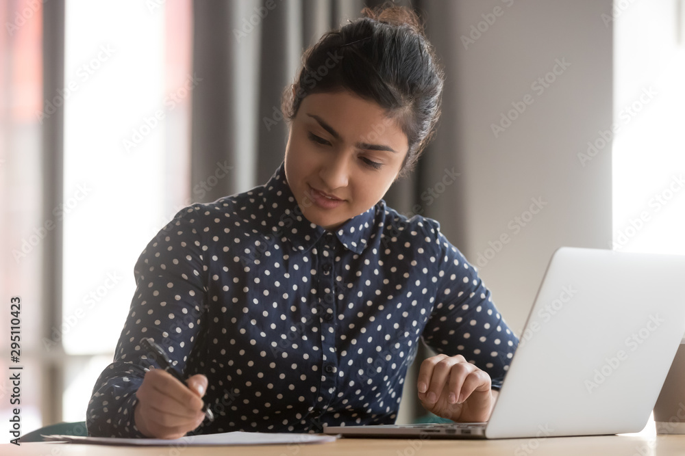 Fototapeta Young indian businesswoman student working studying with laptop making notes