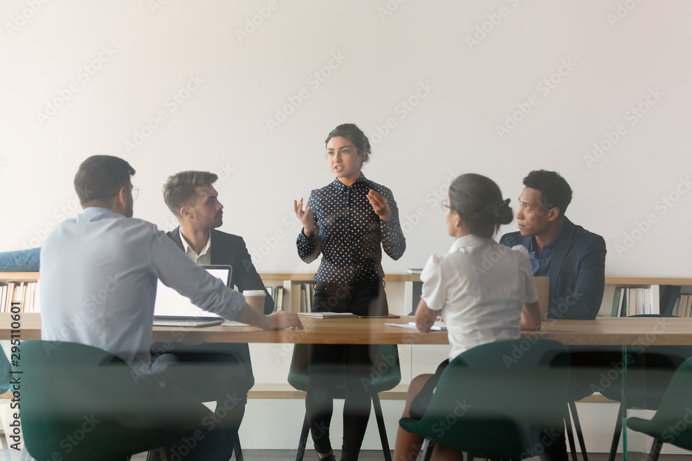 Fototapeta Serious female indian manager talk at group meeting behind glass