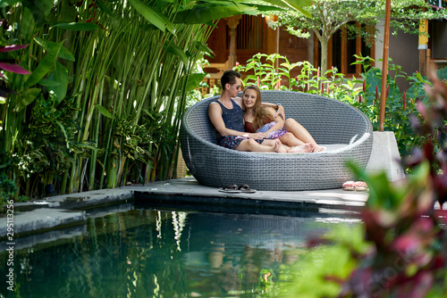 Cadres-photo bureau Gris Candid shot of young caucasian couple lounging in modern chair near luxurious pool of tropical hotel and spa in Bali