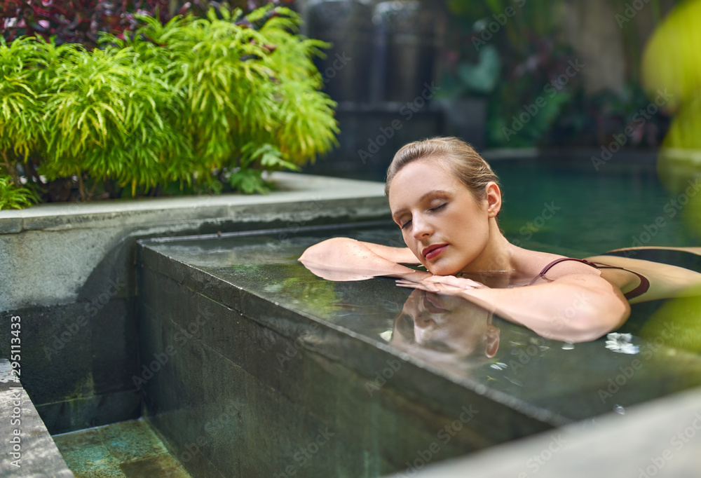 Fototapeta Healthy woman relaxing outdoors in sunny and plant surrounded swimming pool of luxurious resort during tropical vacation in Bali