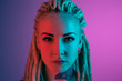canvas print picture - Caucasian young woman's portrait on gradient background in neon light. Beautiful female model with unusual look. Concept of human emotions, facial expression, sales, ad. Looks serious and calm.