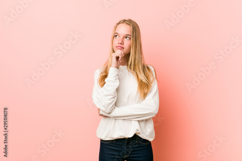 Fotomural  Young blonde teenager woman looking sideways with doubtful and skeptical expression