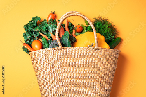 Fototapeta Straw basket with organic vegetables over trendy yellow background