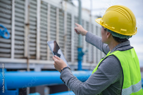 Obraz Engineer with safety helmet at the construction site typing on a digital tablet - fototapety do salonu