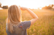 Leinwanddruck Bild - Young blonde woman looking on the sunset. Back