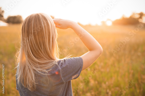 Photographie Young blonde woman looking on the sunset. Back