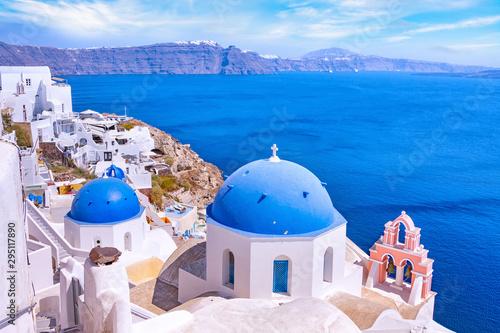 Fototapeta Beautiful Oia town on Santorini island, Greece. Traditional white architecture  and greek orthodox churches with blue domes over the Caldera, Aegean sea. Scenic travel background. obraz