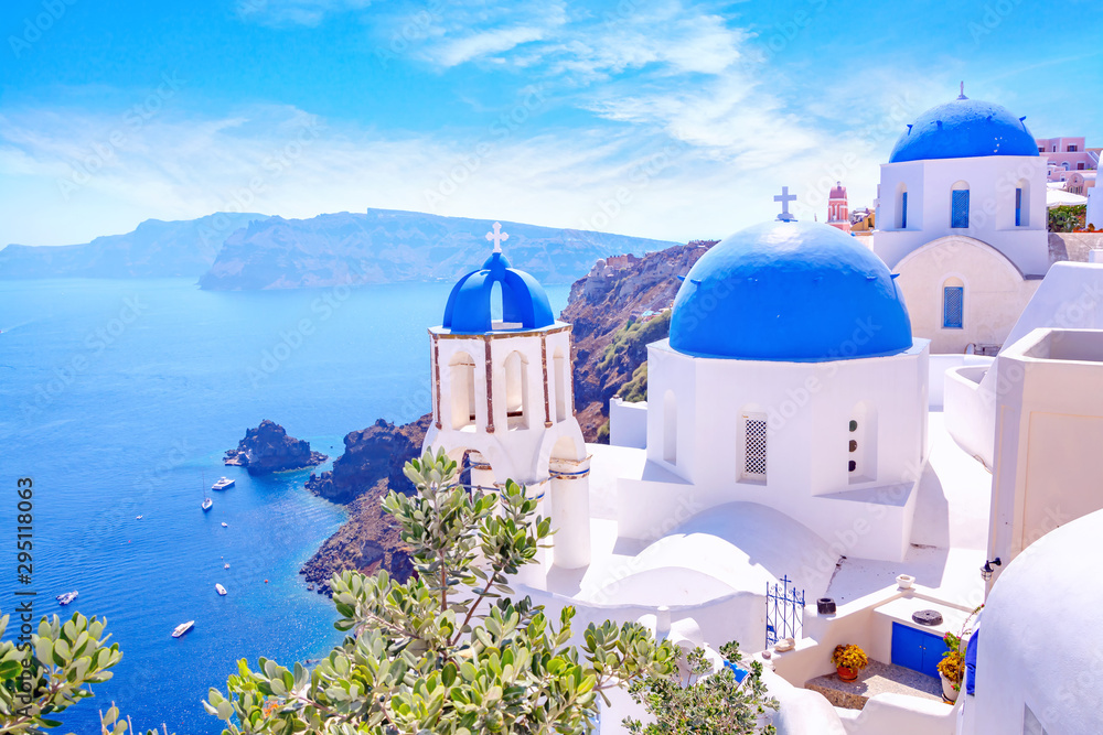 Fototapeta Beautiful Oia town on Santorini island, Greece. Traditional white architecture  and greek orthodox churches with blue domes over the Caldera, Aegean sea. Scenic travel background.