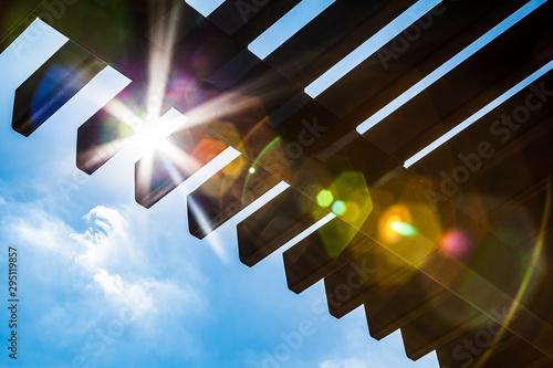 Fototapeta Sun Flare Through A Wooden Pergola obraz