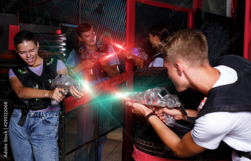Fototapety, obrazy: friends holding colored laser guns during laser tag game
