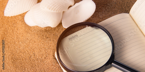 On a notebook lies a magnifier for study and a seashell on the sand Fototapeta