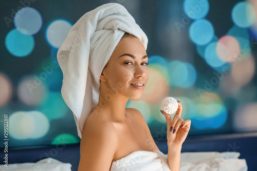 beautiful woman with a towel on her head sitting on the bed and eating cookies, Obraz na płótnie