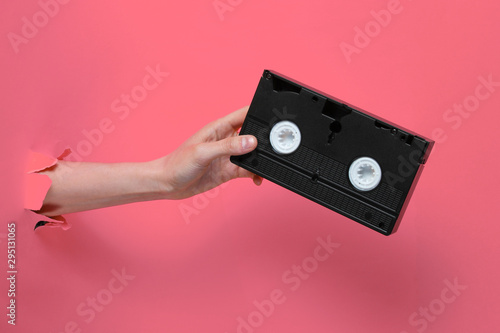 Female hand holds video cassette through torn pink paper background Slika na platnu