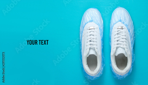Fotografia White sneakers in boot covers on blue background