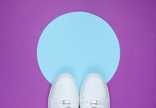 White Sneakers On Purple Background With Blue Pastel Circle For Copy Space. Youth Hipster Concept. Top View