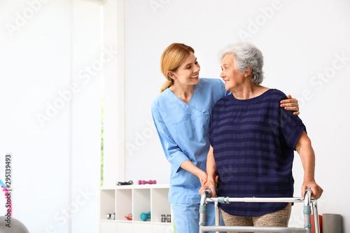 Cuadros en Lienzo Caretaker helping elderly woman with walking frame indoors