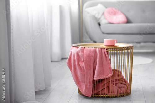 Obraz Side basket table with cup of coffee and blanket in modern room interior - fototapety do salonu