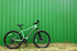 Leinwanddruck Bild - Modern bicycle near green metal fence outdoors. Space for text