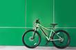 Leinwanddruck Bild - New modern color bicycle near green wall outdoors