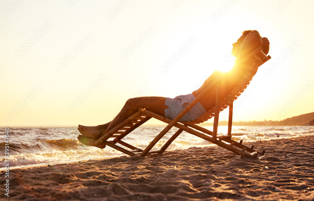 Fototapety, obrazy: Young man relaxing in deck chair on beach near sea