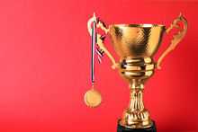 Golden Trophy Cup And Medal On...