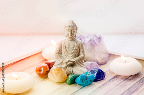 All seven chakra colors crystals stones around sitting Buddha figurine on natural wooden tray Fototapete