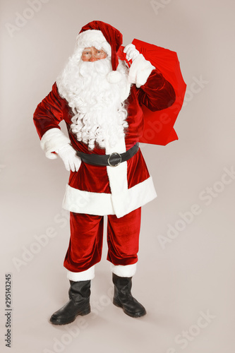 Authentic Santa Claus with bag full of gifts on grey background