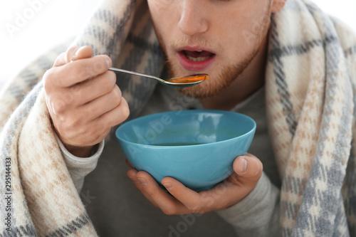 Sick young man eating soup to cure flu, closeup