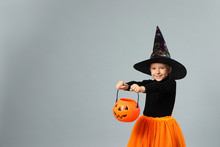 Cute Little Girl With Pumpkin Candy Bucket Wearing Halloween Costume On Grey Background, Space For Text
