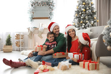 Happy Family With Christmas Gifts On Floor At Home