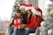 Happy Family With Christmas Gift At Home