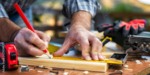 Canvastavla Adult carpenter craftsman with a pencil and the carpenter's square trace the cutting line on a wooden table