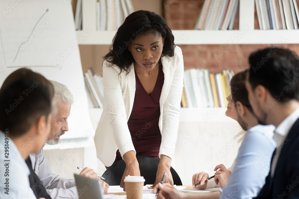 Fototapeta Serious millennial black businesswoman head company briefing in office