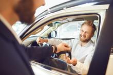 Auto Dealer Shows A New Car To...
