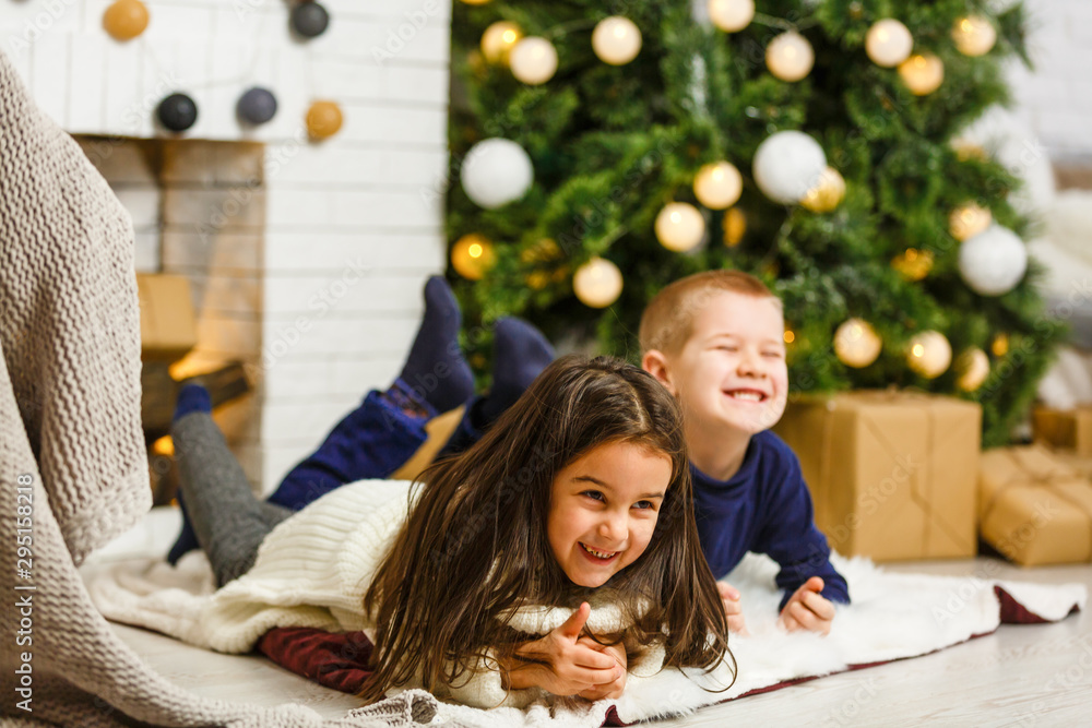 Fototapety, obrazy: Happy little kids decorate Christmas tree in beautiful living room with traditional fire place. Children opening presents on Xmas eve.