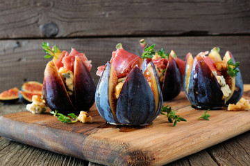 Fig floret appetizers with blue cheese, prosciutto and honey. Side view on a wood serving board.