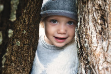 Close Up Of Beautiful Young Girl Model Smiling And Peering Through A Gap Between Tree Trunks In The Woods Wearing Winter Clothes