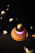 Mousse Cake With Macaroon, Chocolate And Gold Egg On Top, Black Glossy Background And Pieces Of Gold