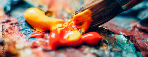 Obraz Modern fine art school. Closeup of paintbrush mixing red and yellow acrylic paint on colorful textured surface. - fototapety do salonu