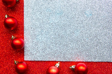 Red Baubles On Glitter Red And Silver Background. Flat Lay, Top View, Copy Space. Merry Christmas And Happy New Year. Beautiful Xmas Greeting Card